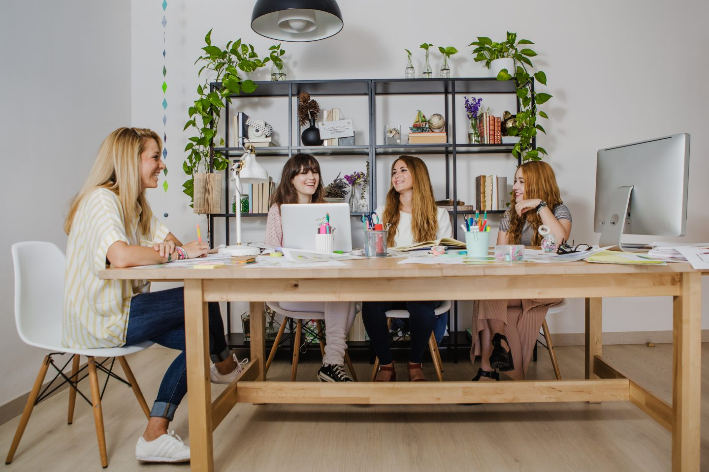 Photo of 4 women around a large desk with laptops.  There are also pens and paper on the desk.